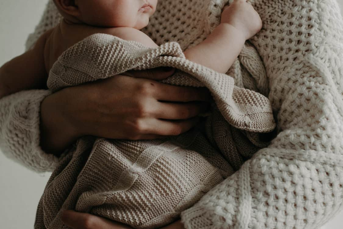 holding baby sweater